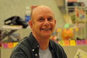 Portrait d'un homme chauve souriant prise dans une librairie.