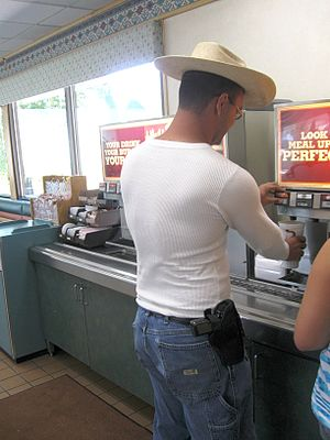 "Politicized issue - Gun control issues such as laws which permit open carry of handguns in public places are ""hot button"" issues. Pictured is a man openly carrying a 9mm Browning Hi Power handgun at a fast food restaurant in Eagle, Colorado."