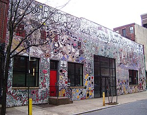 """Painted Bride Art Center - The front of the Painted Bride Art Center, showing Skin of the Bride, a mosaic by Philadelphia artist Isaiah Zagar which covers the entire building; the text along the top says """"The Bride has many suitors, even"""", a reference to Marcel Duchamp's The Bride Stripped Bare By Her Bachelors, Even"""