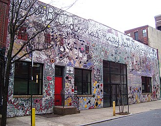 "Painted Bride Art Center - The front of the Painted Bride Art Center, showing Skin of the Bride, a mosaic by Philadelphia artist Isaiah Zagar which covers the entire building; the text along the top says ""The Bride has many suitors, even"", a reference to Marcel Duchamp's The Bride Stripped Bare By Her Bachelors, Even"