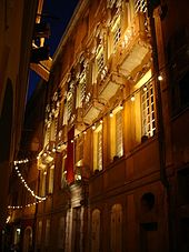 Vue en contre-plongée de la façade d'un palace éclairée de nuit dans une petite rue avec une guirlande d'ampoules zigzaguant entre les murs.