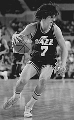 A black and white photo of a man, wearing a basketball uniform that says Jazz with the number 7 below it, is looking to the right.