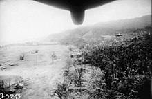 Black and white aerial photograph of an airfield in a jungle clearing. Part of the fuselage of the aircraft is visible at the top of the photograph.