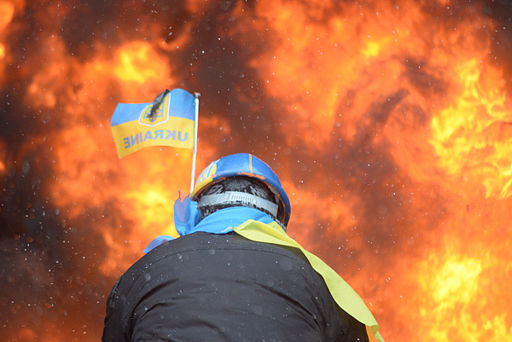 Protester wearing Ukraine state flag colors facing the massive fire set by protesters to prevent internal forces from crossing the barricade line. Kyiv, Ukraine. Jan 22, 2014