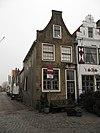foto van Pand met achterhuis en IJsselstenen tuitgevel met rode strekken boven de vensters en geprofileerde topafdekking. Stoep