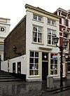foto van Huis met eenvoudige witgeverfde lijstgevel, lage bovenverdieping en schilddak