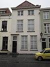 foto van Huis met gebosseerd gepleisterde lijstgevel, kroonlijst op klossen en ingang tussen gecanneleerde pilasters. Plat dak