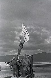 Israeli soldiers stabilize a flag pole whilst another soldier climbs it in order to raise an improvised flag; the soldier is seen about halfway up the flag pole. Other soldiers look on.