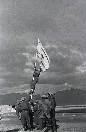 "1948 Arab–Israeli War - Captain Avraham ""Bren"" Adan raising the Ink Flag at Umm Rashrash (a site now in Eilat), marking the end of the war."