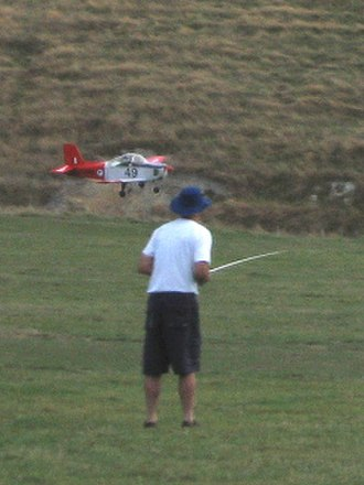 Radio-controlled aircraft - A radio-control flyer (holding a transmitter) guides his aircraft in for a landing