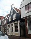 foto van Huis met zadeldak en houten topgevel op geprofileerde lijst