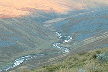 Ribbon of river in shadow reflecting the sky, bending back and forth through a valley between moorland hills of grey scree and brown and green vegitation