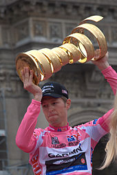 A man wearing a pink jersey while holding a golden trophy.