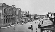 A bustling city street of early 20th-century colonial appearance.