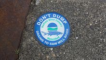 A blue and green circular medallion on a sewer warning that the discharge goes into the river