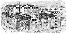 Large factory set up, showing several buildings surrounded by a high wall