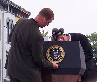 Seal of the President of the United States - A member of the White House Communications Agency (WHCA) placing the seal on the president's lectern.