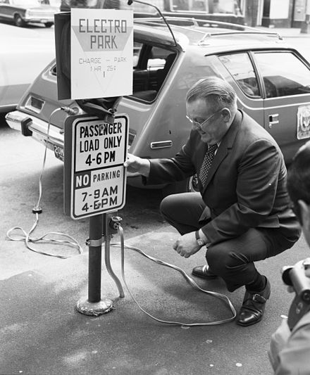 This 1973 photo of a charging station in Seattle shows an AMC Gremlin modified to take electric power; it had a range of about 50 miles on one charge. Seattle City Light Superintendent Gordon Vickery with prototype electric car, 1973 (34772918810).jpg