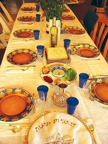 English: Festive Seder table with wine, matza ...