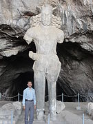 Shapur statue with a man standing in front of it.JPG