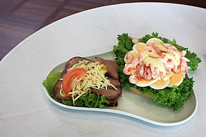 Culture of Denmark - Smørrebrød (Open sandwich), Left: Roast beef with remoulade, grated horseradish and tomato on Danish rye bread. Right: Egg, prawns, lemon and mayonnaise on white bread.