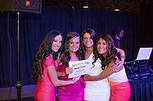 "Four young women pose holding both each other and an award for ""Alpha Gamma Delta: Best Tree"""