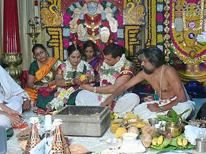 South Indian couple to be wed holding a fruit,...