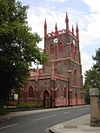 A brick tower with red decorations, including a pierced parapet and crocketed pinnacles