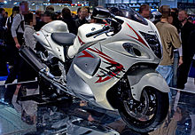 A white motorcycle with fully enclosed bodywork standing upright on a mirrored top platform in a large indoor hall with a crowd of people in the background.