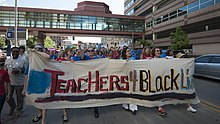 "five protesters carrying a banner that reads ""Teachers 4 Black Liv[banner not visible]"". They lead a crowd filling the street. Some are walking under a skyway with green-blue windows."