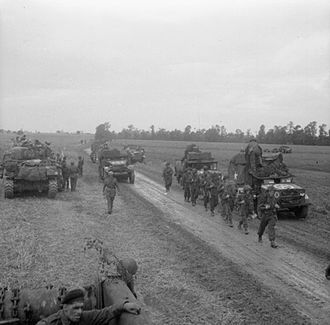 227th Infantry Brigade (United Kingdom) - Men of the 10th Battalion, Highland Light Infantry advance past vehicles of 15th (Scottish) Division during Operation 'Epsom', 26 June 1944. On the left are two Sherman Crab flail tanks.