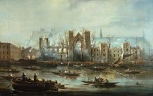 A view of Parliament, burned out, from the South bank of the Thames. The outline of a large gable ended building is visible in the middle of the complex; there is much smoke around the image. Several boats are visible on the river, looking at the building.
