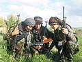 Three YPJ fighters inspect a camera.jpg