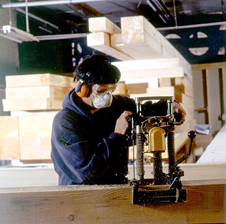 Woodworking joints - A worker uses a mortising machine to shape timber framing joints