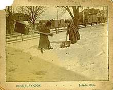 Two adolescent girls shoveling snow after a heavy snowfall.