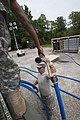 U.S. Army Sgt. William White hands a water nozzle to Spc. Paul Hiers, a water specialist with the 741st Quartermaster Company, South Carolina Army National Guard, after putting purified water into a water tank 130518-Z-XH297-011.jpg