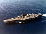 Large aircraft carrier with numerous aircraft on its flight deck.