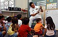 US Navy 030512-N-7217H-002 Mess Management Specialist 2nd Class Raul Pasana, assigned to Fleet Activities Sasebo's Logistics Department, reads a book to E.J. King Elementary School's 2nd grade students in during Armed For.jpg