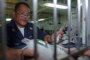 Stored-value card - Disbursing Clerk 1st Class Gene Tecson holds a keypad for a customer to enter his Navy Cash Card personal identification number aboard the amphibious assault ship USS Peleliu (LHA 5). The system eliminates cash and coins from the entire ship and instead requires sailors to add money from their personal bank accounts to one of two systems held on the cash card.