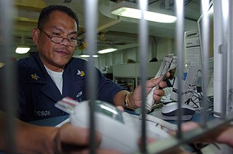 Stored-value card - Image: US Navy 050301 N 9866B 001 Disbursing Clerk 1st Class Gene Tecson holds a keypad for a customer to enter his Navy Cash Card personal identification number