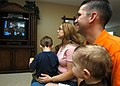 US Navy 050309-N-3019M-001 Personnelman 1st Class Drew Breeden, assigned to the Safeguard-class rescue and salvage ship USS Salvor (ARS 52), and his wife and two sons, watch a tape of Breeden playing the Wheel of Fortune game s.jpg