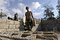 US Navy 050310-N-0411D-006 Builder 3rd Class Alex Martinez of Bayville, N.J., carries cement blocks into the partially completed school building which he and his fellow Seabees are constructing in Gonaives, Haiti.jpg