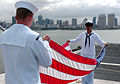 US Navy 050427-N-7130B-099 Fire Controlman 3rd Class Kenneth Breeden, left, is assisted by Aviation Electronics Technician Airman Tonee Barachina in folding the national ensign on the flight deck aboard USS Ronald Reagan (CVN 7.jpg