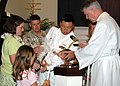 US Navy 050711-N-5783F-002 Lt. Cmdr. Chris Buziak holds his son during a baptism ceremony performed by Father Patrick McCormick at Pearl Harbor Memorial Chapel.jpg