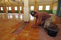 US Navy 051224-N-4374S-002 Builder 3rd Class Jonathan Martinez, assigned to Naval Mobile Construction Battalion Three (NMCB-3), applies a ceramic floor tile during the restoration project at the Providence Hall in St. Elisabet.jpg