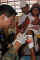 US Navy 060602-M-1837P-003 Navy Lt. Jay Choe unwraps a dressing on the leg of 6-year-old Meilawati Handayani during a follow-up examination at the 3rd Marine Expeditionary Force's (3rd MEF) Mobile Surgical Hospital.jpg