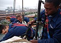 US Navy 070723-N-2893B-001 Working with other USS Constitution Sailors on the ship's mizzenmast, Seaman Apprentice Tyrell Mackey ties a gasket to secure the topsail to the starboard yard.jpg