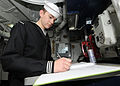 US Navy 100121-N-6233H-018 Boatswain's Mate 3rd Class Nate Long writes in the Petty Officer of the Watch logbook during his watch aboard the aircraft carrier USS George Washington (CVN 73).jpg