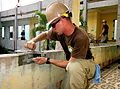 US Navy 100517-N-0827C-005 Engineering Aide Constructionman Christopher Kelly applies cement to cracks at the Hope Center engineering site in Quy Nhon, Vietnam.jpg