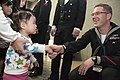 US Navy 101212-N-5758H-024 Musician 2nd Class John Wylie, assigned to the U.S. 7th Fleet Band, Far East Edition, shakes hands with a girl after th.jpg